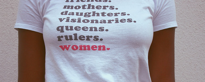 Woman wearing a T-shirt stating: Mothers, Daughters, Visionaries, Queens, Rulers, Women.